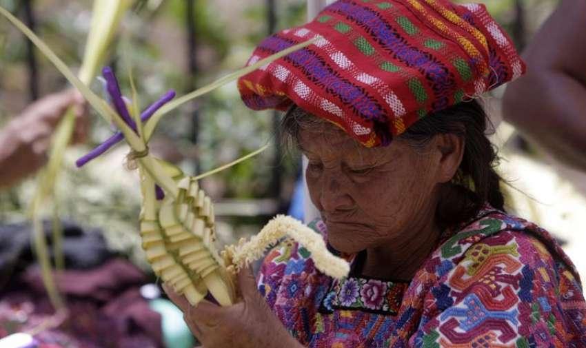 """Una vendedora elabora un ramo que será lanzado durante la procesión Jesús De las Palmas, en Ciudad de Guatemala (Guatemala). La procesión, conocida en Guatemala como """"Jesús de la Borriquita"""", recuerda la entrada de Jesús a Jerusalén. EFE"""