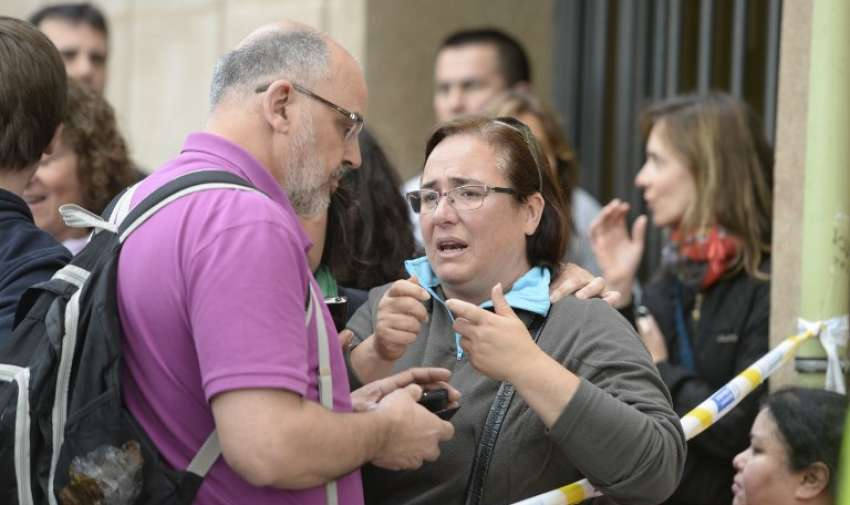 Algunas personas hablan al lado de un cordón de policía en el Instituto Joan Fuster en Barcelona el 20 de abril 2015 después de que un estudiante asesinara a un profesor y dejara a otros cuatro gravemente herido. AFP