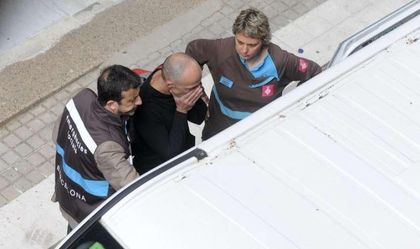 Los miembros del servicio de Emergencias acompañan a un hombre en el Joan Fuster Institue en Barcelona hoy 20 de abril 2015 después de que un estudiante irrumpiera en la escuela armado con una ballesta y matara a un profesor, hiriendo a otros cuatro . AFP