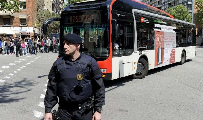 Un policía monta guardia junto a un autobús que transportaba a estudiantes del Instituto Joan Fuster en un autobús en Barcelona el 20 de abril 2015. AFP