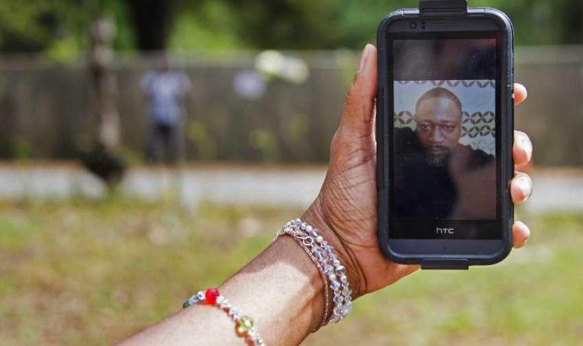 Barbara Scott, primo de Walter Scott , de 50 años de edad, el hombre que fue asesinado después de que fue despedido a ocho veces se escapó de un oficial después de una parada de tráfico , sostiene una foto de Scott en su teléfono celular en North Charleston , Carolina del Sur el 8 de abril de 2015. AFP