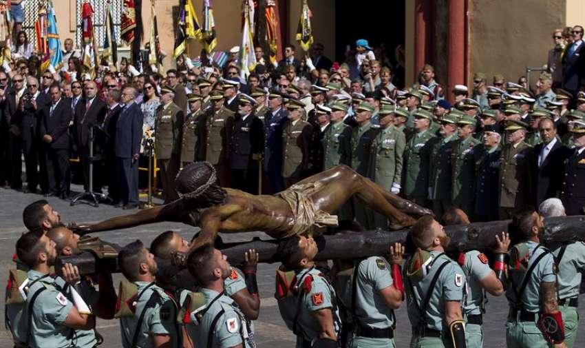 Caballeros legionarios portan la imagen del Cristo de la Buena Muerte, también conocido como el Cristo de Mena, en el traslado de éste al trono donde sale en procesión cada Jueves Santo en Málaga, con 2.500 kilos de peso y que es portado por 235 hombres de trono. EFE