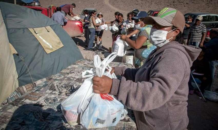 Voluntarios distribuyen bolsas con víveres en la localidad de Paipote (Chile). EFE