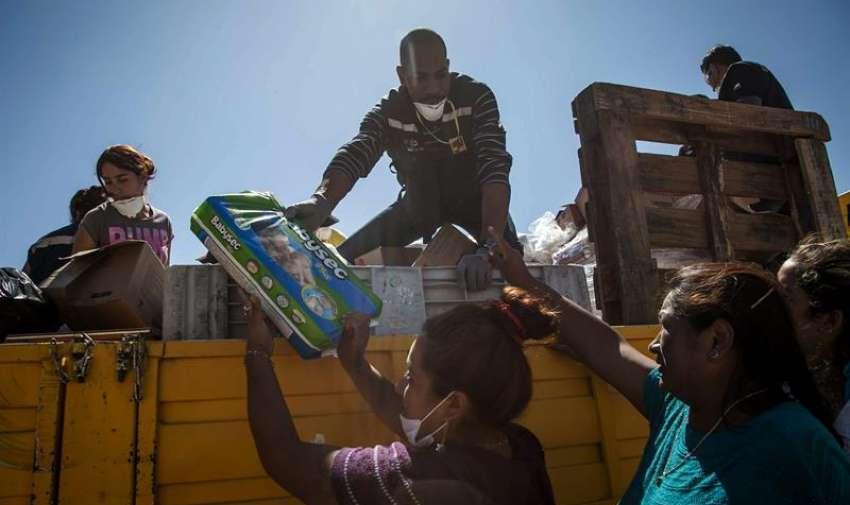 Voluntarios distribuyen bolsas con víveres y ropa. EFE