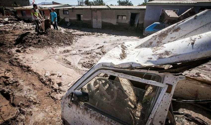 Habitantes participan en la limpieza de una calle anegada de lodo en Paipote, Chile. EFE