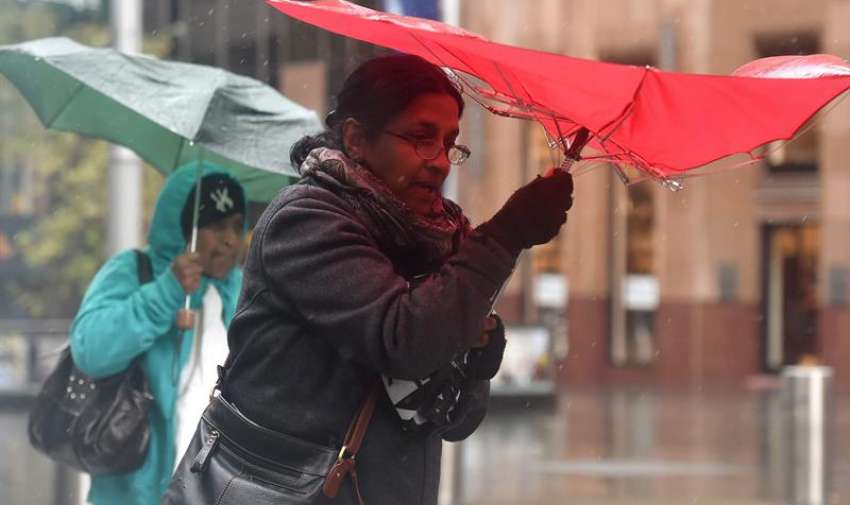 Los peatones se refugian bajo sus paraguas  bajo los paraguas de la lluvia pesada en Sydney , Australia , 20 de abril de 2015. La lluvia y vientos dañinos promedio de 55 a 70 Km / h con ráfagas de unos 100 km se pronostican para desarrollar a lo largo de la franja costera de la zona metropolitana de Sydney . EFE