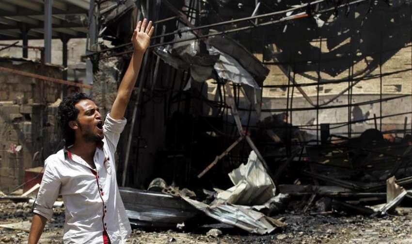 Un hombre grita para pedir ayuda tras un supuesto bombardeo de la colaición árabe en Saná, Yemen, el 20 de abril del 2015. EFE