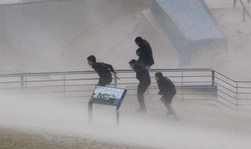 Varios chicos buscan refugio de los fuertes vientos en la playa Bondi durante una fuerte tormenta en Sídney, Nueva Gales del Sur (Australia) hoy, martes 21 de abril de 2015. EFE