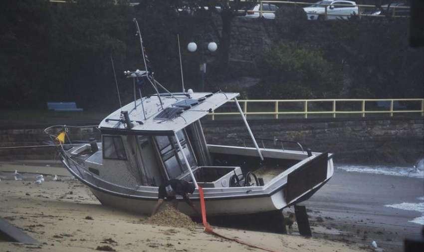 Un hobmre excava alrededor de su barco en la playa en Manly Cove, en Sídney, Nueva Gales del Sur (Australia) hoy, martes 21 de abril de 2015. EFE