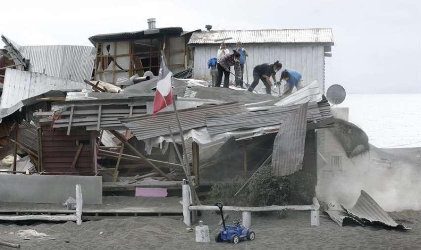 Un grupo de personas limpia el tejado de una casa parcialmente destruida por el peso de la ceniza emanada por el volcán Calbuco. EFE