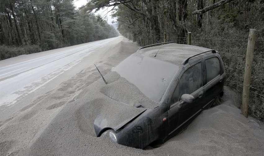 Un vehículo permanece cubierto de ceniza a un lado de una vía, en Chile. EFE