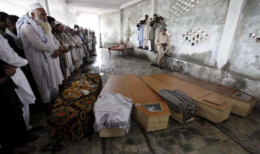 Amigos y familiares de las víctimas rezan junto a sus ataúdes en Peshawar (Pakistán) hoy, lunes 27 de abril de 2015. Al menos 50 personas murieron y 200 resultaron heridas a consecuencia de las lluvias torrenciales y los fuertes vientos que han asolado el noroeste de Pakistán. EFE