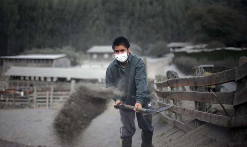 Un hombre retira ceniza volcánica, tras la erupción del volcán Calbuco, en la localidad de Ensenada, en la región de Los Lagos, en sur de Chile. EFE