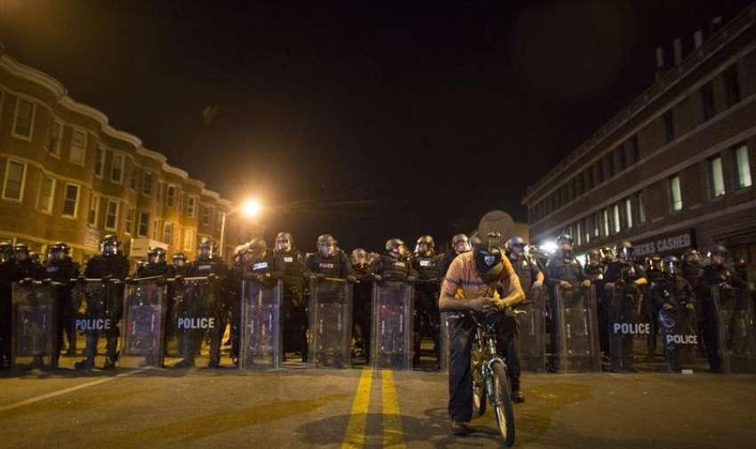 Un manifestante permanece en su bici ante policías antidisturbios en Baltimore (Estados Unidos). EFE