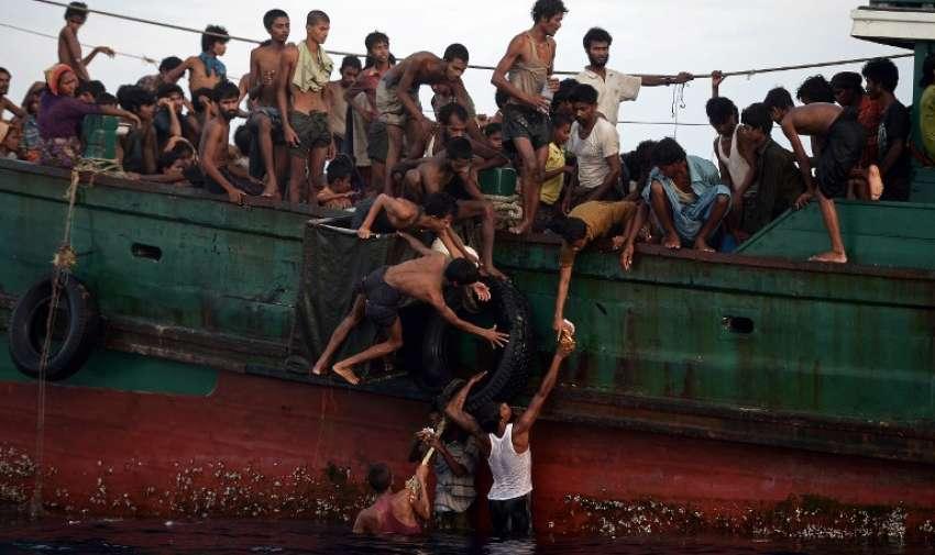 Migrantes rohingya pasan los suministros de alimentos se redujeron en un helicóptero del ejército tailandés a los demás a bordo de un barco a la deriva en aguas de Tailandia fuera de la isla sur de Koh Lipe en el mar de Andamán, el 14 de mayo de 2015. AFP