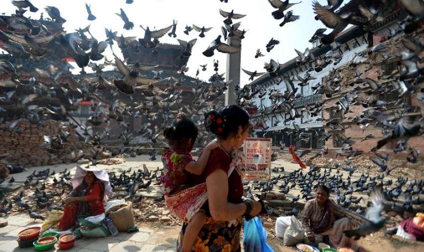 Palomas vuelan por encima de los vendedores ambulantes de Nepal, cerca de la Plaza Durbar de Katmandú el 20 de mayo 2015. AFP