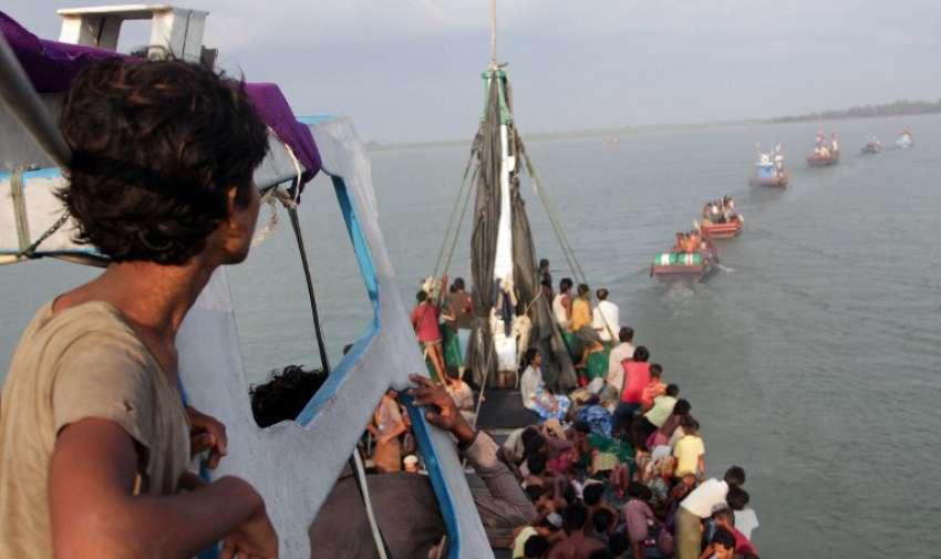 Barcos de pescadores de Aceh (en el frente) remolcar un barco de inmigrantes rohingya en su barco frente a la costa cerca de la ciudad de Geulumpang en el distrito de Aceh de Indonesia oriental de la provincia de Aceh antes de ser rescatado el 20 de mayo de 2015. AFP