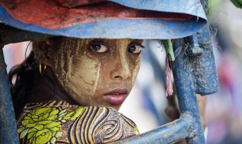 Esta foto tomada el 21 de mayo 2015 muestra una mujer de la etnia rohingya musulmana mirando hacia atrás mientras se monta un tuk tuk cerca de un campamento establecido fuera de la ciudad de Sittwe, en el estado de Rakhine de Myanmar. AFP