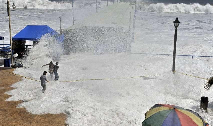 La gente trata de protegerse de las olas en La Libertad, 34 km al sur de San Salvador, el 3 de mayo de 2015.