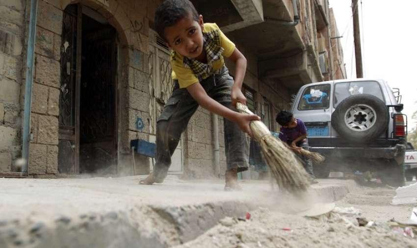 Niños yemeníes barren la acera llena de basura como camiones de basura apenas se ejecutan debido a una grave escasez de combustible en la capital Saná , el 4 de mayo de 2015. AFP