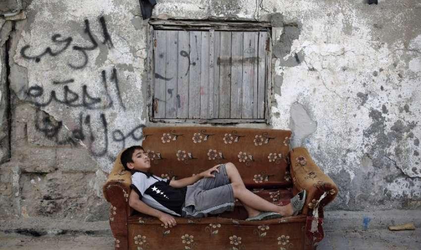 Un niño palestino descansa en un viejo sillón en frente de una casa en ruinas el 22 de mayo de 2015, de Gaza. AFP
