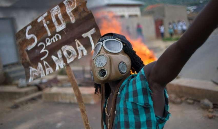 """Un manifestante de Burundi con una máscara de gas y sosteniendo un cartel que dice """"Deja las tercio de mandatos """" cantos cerca de una barricada en llamas en el barrio Mugasa de Bujumbura el 6 de mayo de 2015. AFP"""