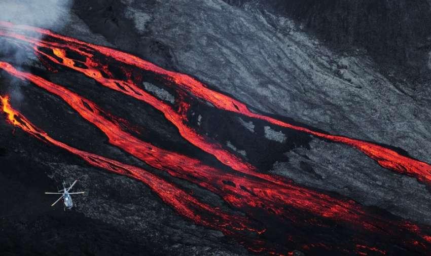 Un helicóptero sobrevuela la lava del volcán  del Piton de la Fournaise en Francia. AFP