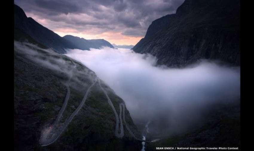 """""""La foto fue tomada desde una carretera montañosa en Trollstigen, en el occidente de Noruega. Tuve la suerte de vivir aquí por dos meses, durante el verano. Una noche, vi como la neblina cubría el valle, así que salí en mi auto para presenciar el sol de medianoche"""", explicó el fotógrafo Sean Ensch. BBC"""