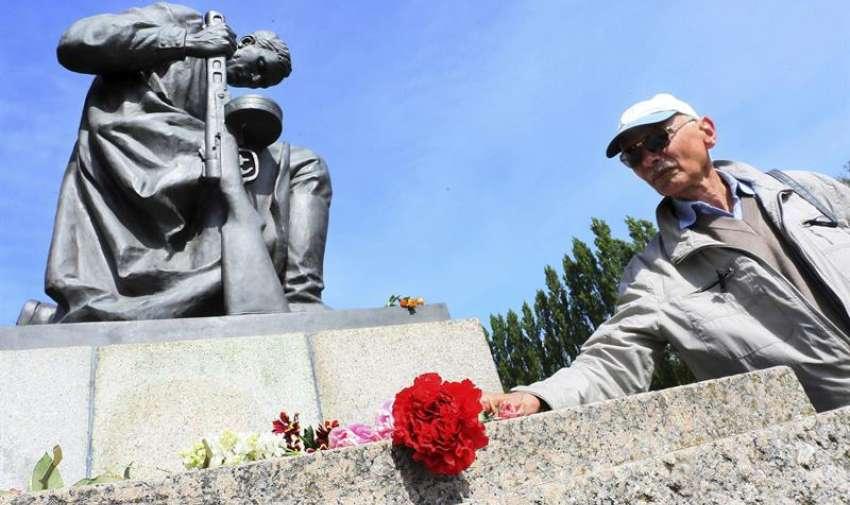 Un hombre coloca un clavel rojo frente al cenotafio soviético en el parque de Treptow en Berlín, Alemania, hoy, 8 de mayo de 2015. EFE
