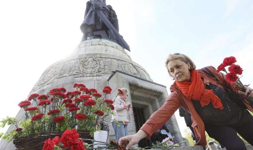 Una mujer coloca claveles rojos frente al cenotafio soviético en el parque de Treptow en Berlín, Alemania, hoy, 8 de mayo de 2015. El Parlamento alemán conmemora hoy el 70 aniversario del fin de la Segunda Guerra Mundial tras la capitulación del Tercer Reich, en una acto solemne al que asisten el presidente del país, Joachim Gauck, y la canciller, Angela Merkel. EFE