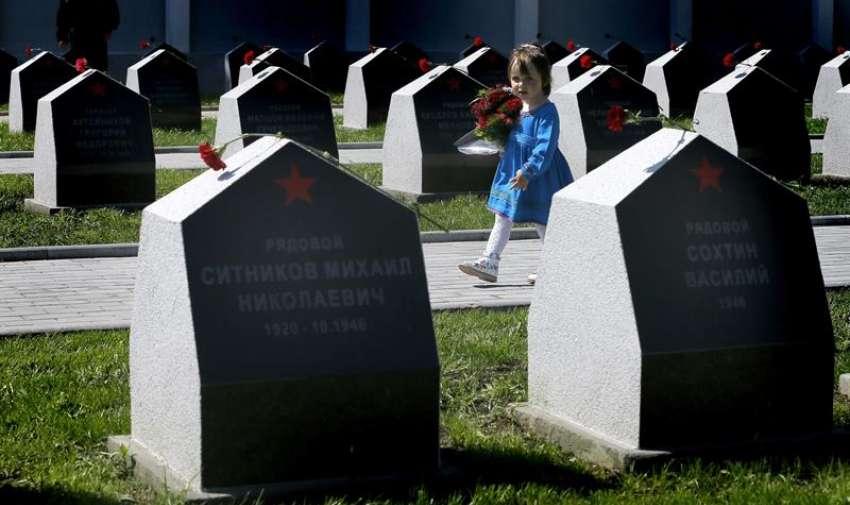Una niña rusa sostiene un ramo de flores durante una ceremonia en recuerdo de los soldados rusos que murieron durante la II Guerra Mundial en Bucarest, Rumanía, hoy, viernes 8 de mayo de 2015. Soldados de la guardia de honor, veteranos de guerra y escolares, entre otros, asistieron a la ceremonia celebrada con motivo del setenta aniversario del fin de la II Guerra Mundial. EFE