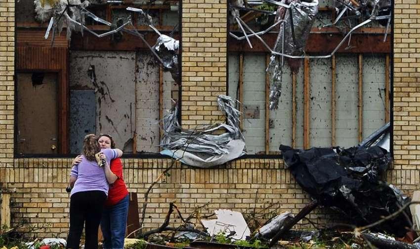 Dos mujeres se abrazan frente a la Escuela Secundaria de Van, destruída tras el fuerte tornado que el pasado 9 de mayo golpeó el norte del estado de Texas, Estados Unidos, hoy, 11 de mayo de 2015. EFE