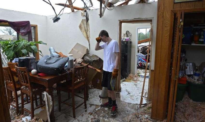 Un hombre trata de recoger algunas de sus pertenencias en su domicilio, destruído tras el fuerte tornado que el pasado 9 de mayo golpeó el norte del estado de Texas, Estados Unidos, hoy, 11 de mayo de 2015. EFE