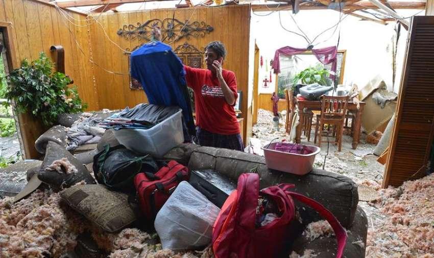 Una mujer recopila algunas de sus pertenencias en su domicilio, destruído tras el fuerte tornado que el pasado 9 de mayo golpeó el norte del estado de Texas, Estados Unidos, hoy, 11 de mayo de 2015.
