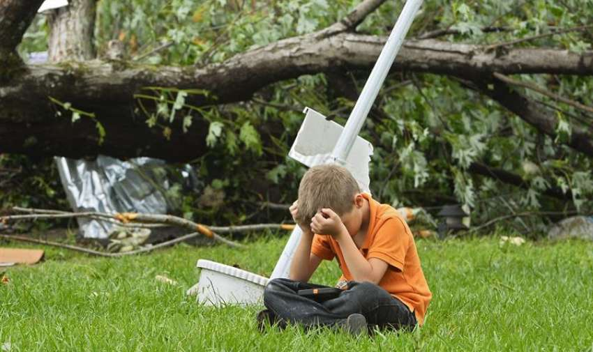 Un niño permanece sentado junto a una residencia destruída tras el fuerte tornado que el pasado 9 de mayo golpeó el norte del estado de Texas, Estados Unidos, hoy, 11 de mayo de 2015. EFE