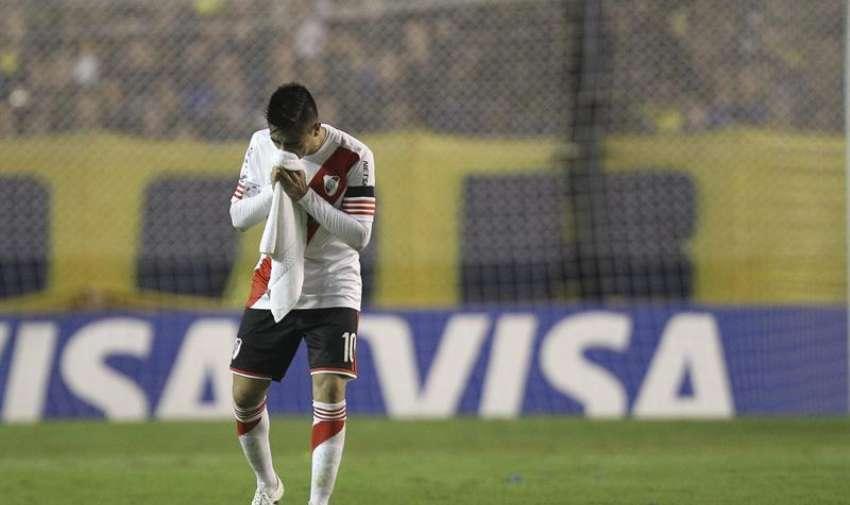 Gonzalo Martínez de River Plate se limpia el rostro luego de que lanzaran gas pimienta desde la tribuna. EFE