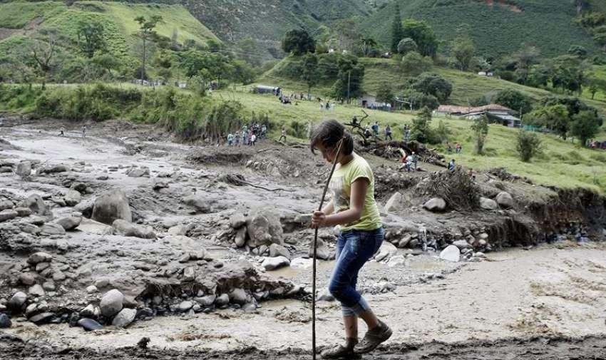 Una niña camina frente a los destrozos ocasionados por una riada en la quebrada Liboriana. EFE