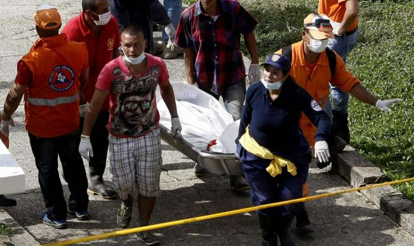 Habitantes y rescatistas trasladan el cuerpo de una víctima de una riada ocasionada por la quebrada Liboriana en Colombia. Foto: EFE