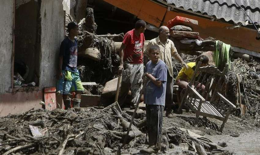 Habitantes limpian los escombros causados por una riada de la quebrada Liboriana. EFE