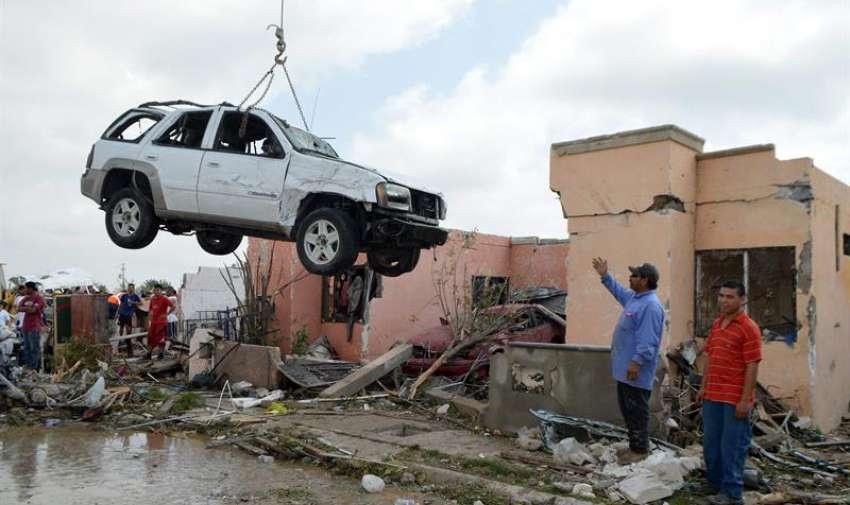 Una grúa levanta un vehículo tras el paso de un tornado  en Ciudad Acuña, norte de México. EFE
