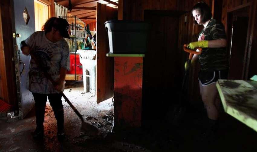 Kimmy Gooding y Courtney Magil ayudan a limpiar la cocina de una casa afectada, a las orillas del río Blanco, en Wimberly, Texas (EE.UU.) EFE