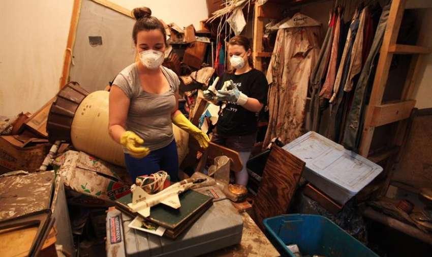 Ashley Hryszko (i) y Haley Hryszko ayudan a limpiar una vivienda afectada de una amiga,  a las orillas del río Blanco, en Wimberly, Texas (EE.UU.). EFE