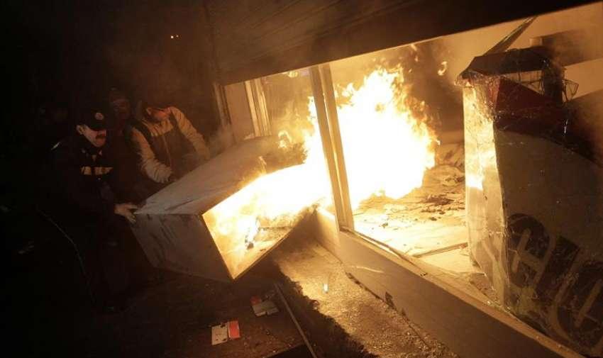 Un grupo de hombres saca un mueble en llamas de una farmacia saqueada, en el centro de Santiago de Chile durante los incidentes tras una marcha convocada por la Confederación de Estudiantes de Chile (Confech). EFE