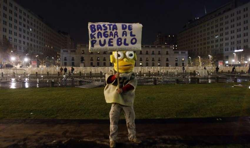 Una persona se manifiesta frente al Palacio de la Moneda en el centro de Santiago (Chile) durante una marcha convocada por la Confederación de Estudiantes de Chile (Confech) y movimientos ciudadanos, en contra de la represión policial en las manifestaciones estudiantiles. EFE