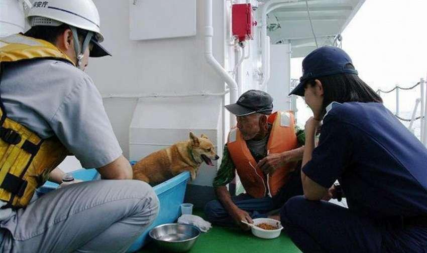 Fotografía distribuida por la Guardia Costera de Japón que muestra a un residente de la isla de Kuchinoerabu y a su perro tras ser evacuados a causa de la erupción del volcán Shindake, en la prefectura de Kagoshima (Japón). EFE