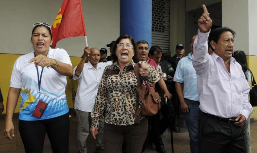 Juan Cervantes vicepresidente nacional de la UNE, se apostó en los exteriores de las oficinas de FCME, para reclamar por la intervención del BIESS. Luis Chancay, miembro de la UNE fue detenido por promover disturbios. Fotos: API
