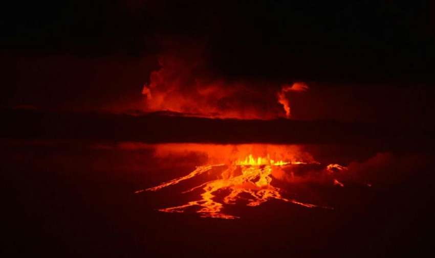 Fotografía cedida hoy, lunes 25 de mayo de 2015, por la Dirección del Parque Nacional Galápagos de la erupción del volcán Wolf, situado en la isla Isabela, del archipiélago ecuatoriano de Galápagos, y que alberga la única población de iguanas rosadas del mundo, que junto con las tortugas del lugar, no se verán afectadas por la erupción debido a la dirección que está tomando el flujo de la lava, según el Parque Nacional. EFE