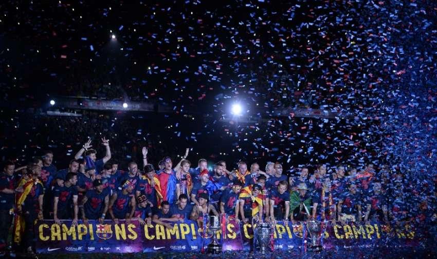 Jugadores del Barcelona posan con los tres trofeos , ya que toman parte en las celebraciones por su victoria sobre la Juventus , un día después de la final de fútbol de la UEFA Champions League, en el estadio Camp Nou en Barcelona el 7 de junio de 2015.. AFP