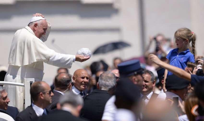 Papa Francisco cambia su gorro con una niña durante su audiencia general semanal en la Plaza de San Pedro el 10 de junio de 2015 el Vaticano. AFP