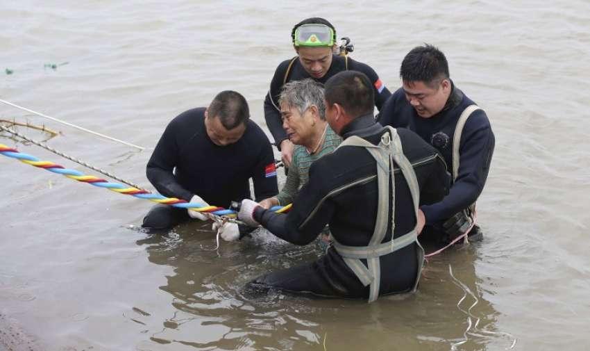 """Un pasajero de edad avanzada ( C ) es escoltado a la orilla del río después de ser rescatado de la Dongfangzhixing o """" Estrella de Oriente """" buque que se hundió en el río Yangtze en Jianli , provincia central china de Hubei el 2 de junio de 2015."""